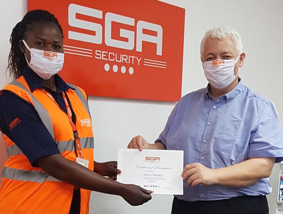 SGA-Security-best-performing-guard-Mercy-Naliaka-receives-a-certificate-and-cash-award-from-the-Country-Director-Jeremy-Van-Tongeren-to-appreciate-role-of-female-guards..jpg